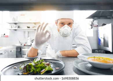 health, safety and pandemic concept - male chef cook wearing face protective mask or respirator for protection from virus disease with plate of soup and salad showing ok sign at restaurant kitchen