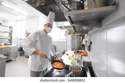 健康と安全、パンデミックのコンセプト – 男性シェフが、レストランのキッチンでフライパンで、ウイルス病の調理用食品から保護するために、顔を保護する医療マスクを身に着けている