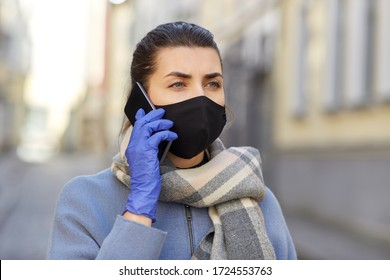 health, safety and pandemic concept - young woman wearing black face protective reusable barrier mask outdoors calling on smartphone