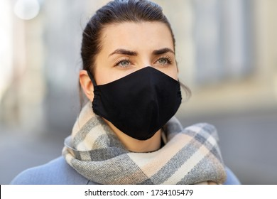 Gesundheit, Sicherheit und Pandemiekonzept - junge Frau, die im Freien eine wieder verwendbare Barrieremaske mit schwarzer Gesichtshaut trägt