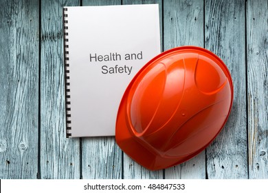 Health and safety register with helmet in closeup