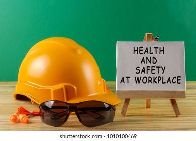 HEALTH AND SAFETY AT WORKPLACE CONCEPT. Yellow hardhat safety helmet,safety glass and ear plug.