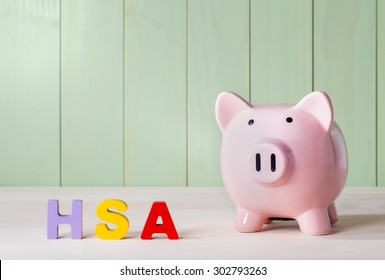 Health Savings Account HSA concept with pink piggy bank, wood block letters and green background