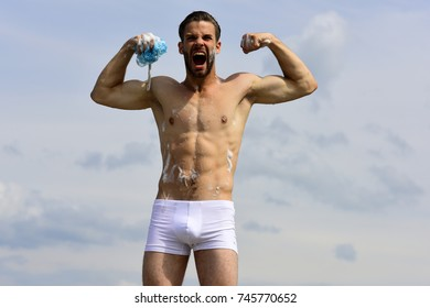 Health and sexuality concept. Macho holding sponge and shouting like beast. Man with unshaved face on clear sky background. Male body with sexy torso. Man in underpants covered with foam shows muscles