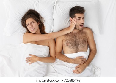 Health and snoring concept. Stressful brunette female pushes away snore husband who distrubes to have good sleep, feels unhappy, doesn`t know how to wake up early tomorrow and not oversleep work