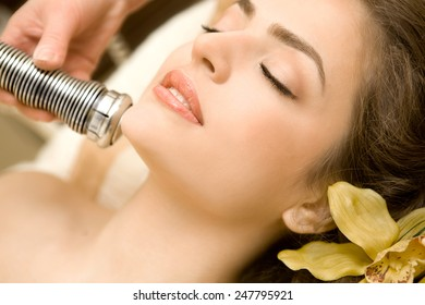 Health Spa: Close-up of Beautiful Relaxing Young Woman Having Facial Massage (electrolysis), with Orchid in Long Brown Hair