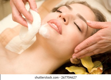 Health spa: close-up of a beautiful relaxing woman having facial massage with a talcom powder