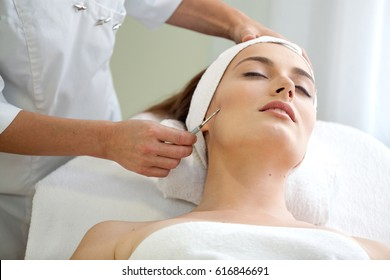 Health spa: close-up of beautiful relaxing young woman having facial massage (electrolysis), with orchid in long brown hair.
