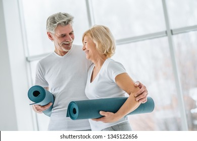 Health and sport concept. Senior couple with yoga mats in the gym.