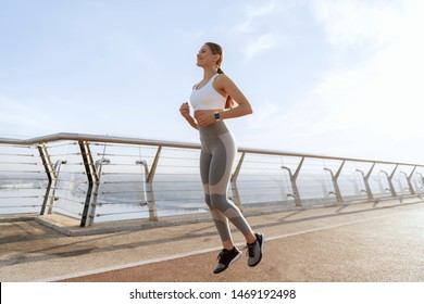 Health and sport practice. Young happy athletic woman in sport wear doing run in the morning