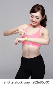 Health sport woman wearing smart watch device with touchscreen doing exercises isolated on gray background, asian beauty