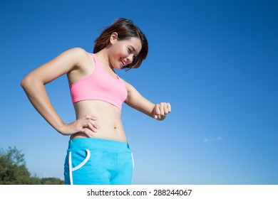 Health sport woman wearing smart watch device with touchscreen doing exercises with blue sky, asian beauty