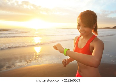 Health sport young woman run and look wear smart watch device with touchscreen on the beach at sunrise, asian