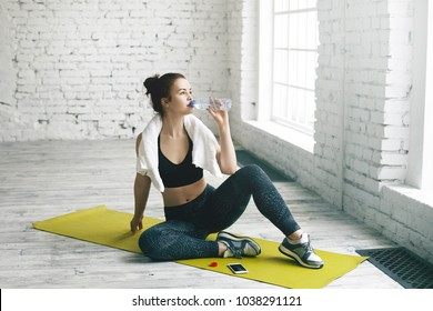 Health, sports, fitness, diet and weight loss concept. Beautiful young brunette female wiping sweat with towel after physical workout, sitting on mat and drinking fresh water out of plastic bottle