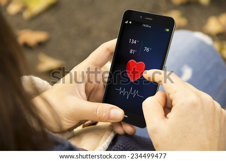 health technology and modern lifestyle concept: young woman using a health app at the park