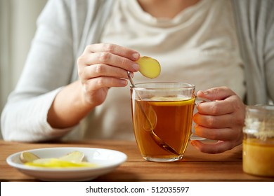 health, traditional medicine and ethnoscience concept - close up of woman adding ginger to tea cup with lemon and honey