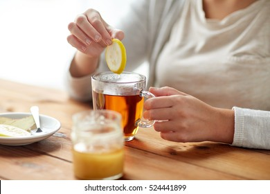 health, traditional medicine and ethnoscience concept - close up of ill woman drinking tea with lemon, honey and ginger at wooden table