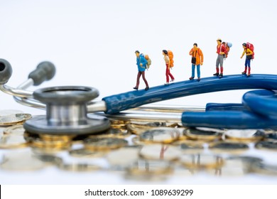 Health and travel insurance, miniature people, traveler with backpack walking on  stethoscope. Business, health care, and traveling concept.