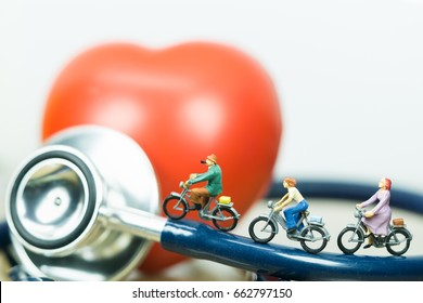Health and travel insurance, miniature people: small figures riding  on stethoscope and red heart. Business, health care, and traveling concept.