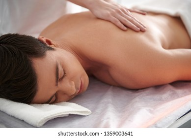 Health treatment concept. Close up portrait of young attractive brunette male enjoying massage of back making by female therapist in spa center