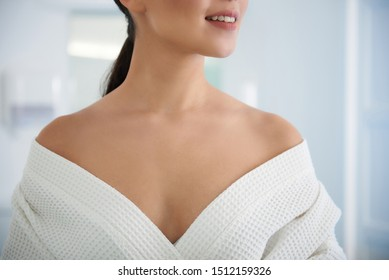 Health treatment concept. Close up portrait of graceful and careful decollete of asian woman undressing her bathrobe before spa procedure