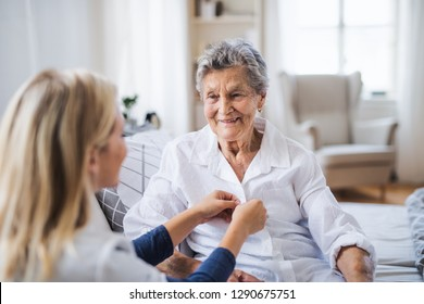 A health visitor helping a sick senior woman sitting on bed at home.