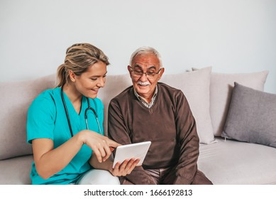 Health visitor and a senior man during home visit. A female nurse or a doctor showing test results on a tablet. Senior patient and caregiver using tablet. I found some entertainment for you