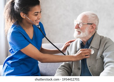 Health visitor and a senior man during home visit. Doctor checking heartbeat examining elder retired man at home. Seniors heart diseases, cardiology concept.