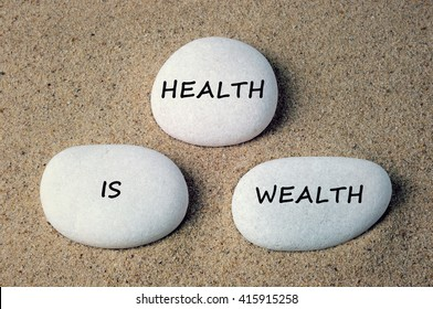 Health is wealth text on white zen stones on sand background