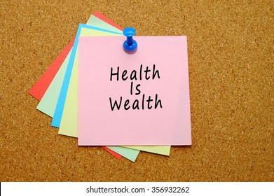 Health is wealth written on color sticker notes over cork board background.