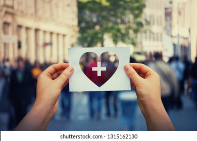 Health and wellbeing global issue as human hands holding a paper sheet with heart and cross icon over a crowded street background. Healthcare medical insurance, good life concept.