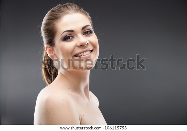 Health woman isolated on gray background. Close up face portrait of toothy smiling girl. Young happy model studio posing