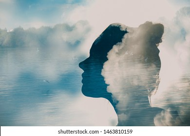 Health of woman. Silhouette of young woman head on background of clouds, water and birds
