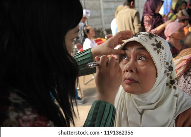 a health worker is examining the eyes of a patient at a health social service event in Surabaya Indonesia on April 12, 2013