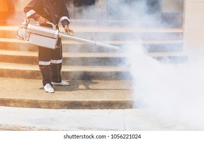 health worker of gesture spray or fogging mosquito repellent or fumigates areas as parts of anti dengue fumigation drive to curb breeding site for mosquito cause dengue fever,Zika Virus or Malaria.
