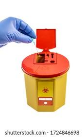 El trabajador sanitario arroja desechos agudos a la basura médica. Tamaño de bolsillo de la basura médica de 1,3 litros. Riesgo biológico amarillo contaminado por el médico contenedor de desechos clínicos aislado en el fondo blanco.