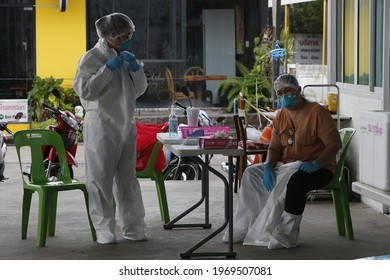 Health workers measure the temperature of a venders before collects a nasal swab sample at a fresh market in Nonthaburi Province, a suburb of Bangkok on May 7, 2021.