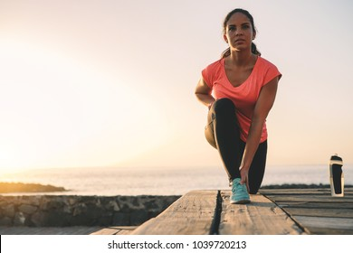 Health young woman stretching next the ocean during a magnificent sunset - Sporty girl work out on the beach - Sport, healthy lifestyle concept