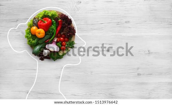 Health in your brain. Fresh vegetables in woman head symbolizing health nutrition on gray background, panorama, copy space