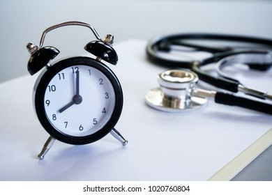 Healthcare concept. Alarm clock and stethoscope on clipboard pad with selective focus.