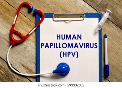 Healthcare concept. Stethoscope, syringe, pen and clipboard written with HUMAN PAPILLOMAVIRUS (HPV) on wooden background.
