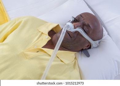 Healthcare concept,African, American Man with obstructive sleep apnea sleeping well with cpap machine ,Man laying in bed wearing cpap mask, on white