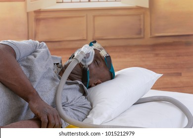 Healthcare concept,African, American Man with obstructive sleep apnea sleeping well with cpap machine ,Man laying in bed wearing cpap mask, in a luxery bedroom