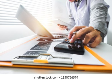 Healthcare costs and fees concept.Hand of smart doctor used a calculator and tablet for medical costs at modern hospital in sun light