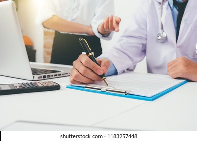 Healthcare costs and fees concept.Hand of smart doctor used a calculator for medical costs at modern hospital in sun light,warm colours sun light