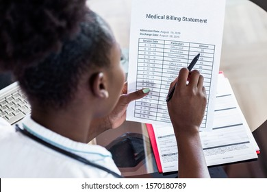 Healthcare costs and fees concept.Hand of smart doctor calculating medical costs in modern hospital. Doctor completing a Medical Claim Form by Stethoscope