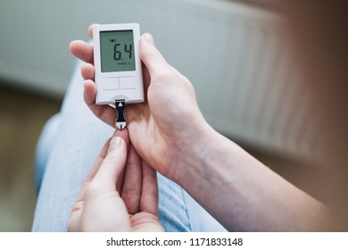 Healthcare and diabetes concept - a young woman measures her blood sugar levels with a glucose meter.