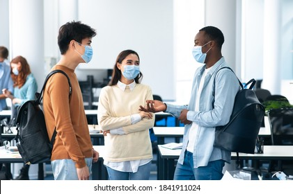Healthcare, Education, Lifestyle And People Concept. Group of smiling diverse international students wearing protective medical masks and talking, standing in lecture hall at the university - Shutterstock ID 1841911024