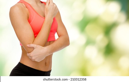 healthcare, fitness and medicine concept - sporty woman with pain in elbow