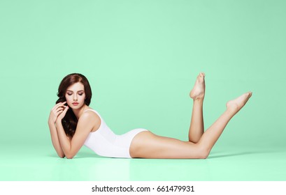 Healthcare, fitness and summer concept. Sporty woman posing in white swimsuit over green background.